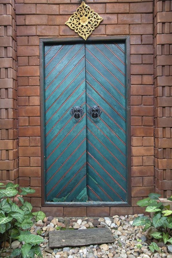 Roczników zieleni drewniani dwoiści drzwi brąz ściana z cegieł fotografia royalty free