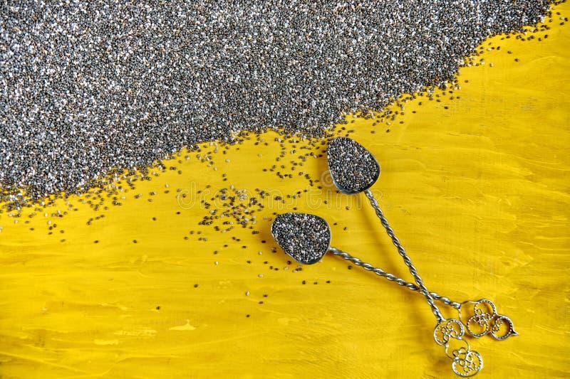 Rocznik łyżki z świeżymi chia ziarnami na żółtej drewnianej desce Surowy zdrowy chia superfood Rozrzuceni chia ziarna na drewnian zdjęcie royalty free