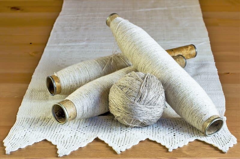 Rocznik cewy z naturalnymi bieliźnianymi niciami i handmade koronkowy tablecloth na drewnianym tle zdjęcia stock