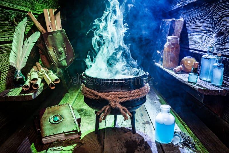 Rocznik czarownicy garnek z magiczną miksturą, błękitnymi napojami miłosnymi i książkami dla Halloween, zdjęcia stock