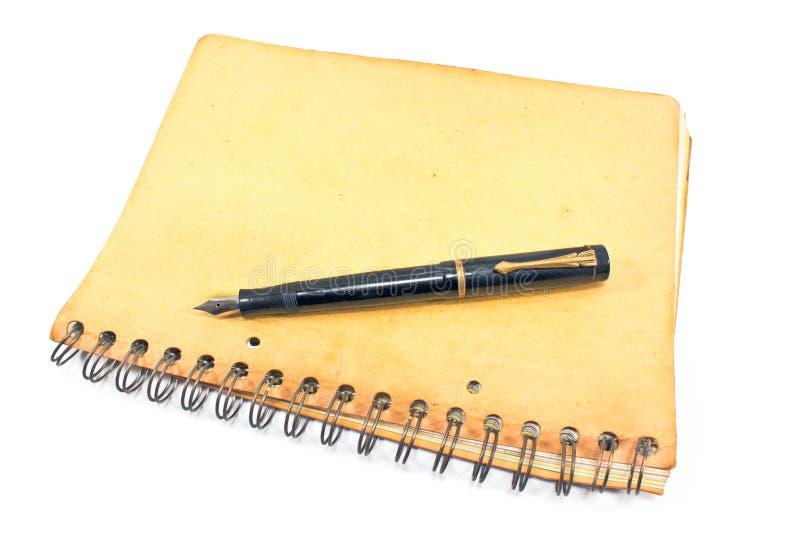 Rocznik fontanny pióro na starym ślimakowatym notatniku obraz stock