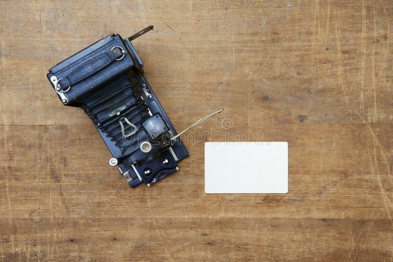 Rocznik fotografii kamera z pustą fotografii ramą na drewnianym stole zdjęcie stock