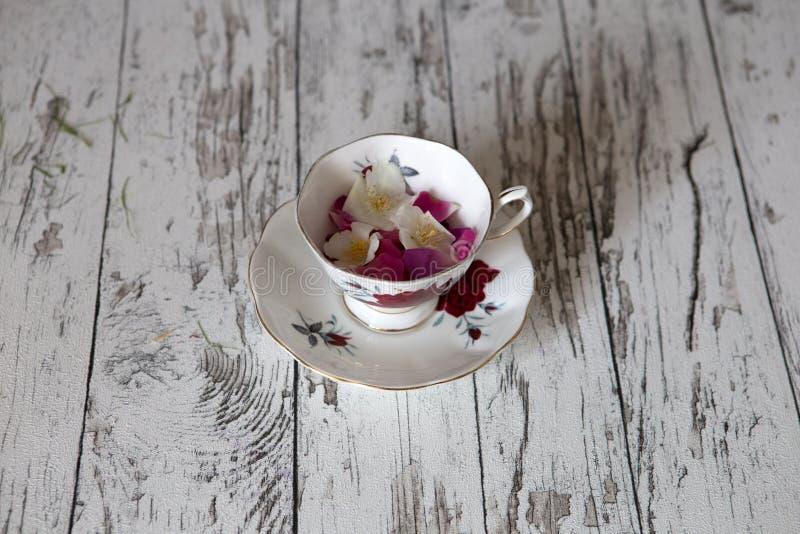 Rocznik Herbaciana filiżanka na nieociosanym bielu stole obrazy stock