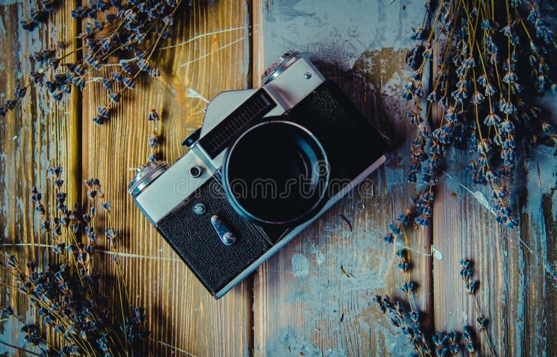 Rocznik kamera na brązu drewnianym tle z lawendą kwitnie flatlay fotografia stock