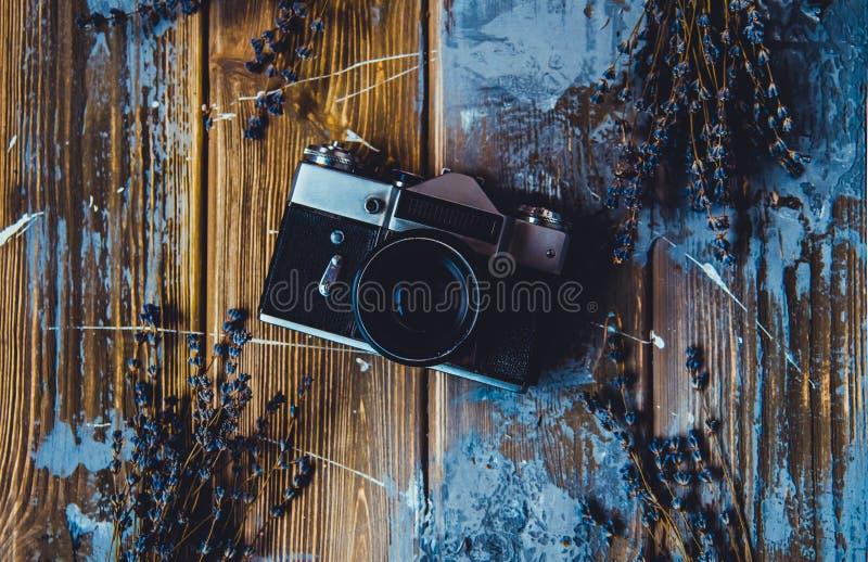Rocznik kamera na brązu drewnianym tle z lawendą kwitnie flatlay fotografia royalty free