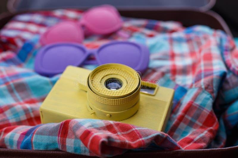 Rocznik kamera, okulary przeciwsłoneczni i w kratkę koszula w otwartej walizce, zdjęcia royalty free