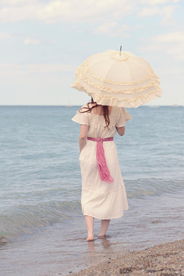 Rocznik kobieta na plaży z parasol obraz royalty free