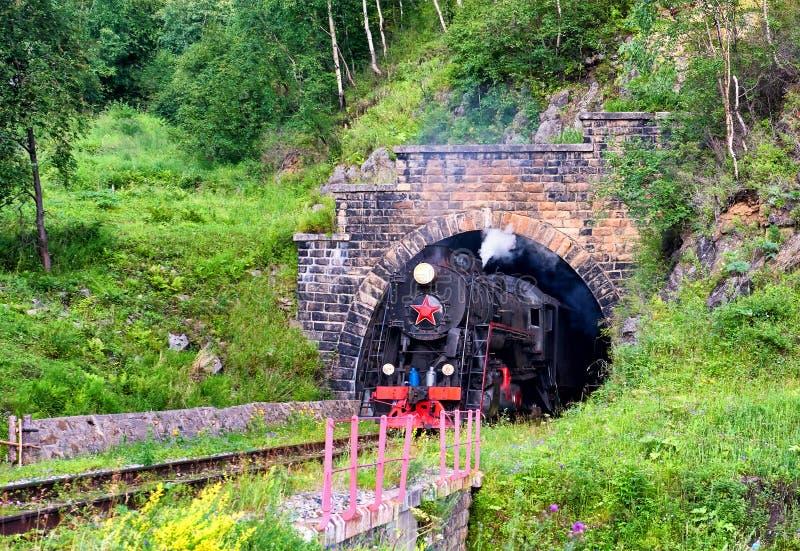 Rocznik kontrpary pociąg opuszcza od łuku linia kolejowa tunel obraz stock