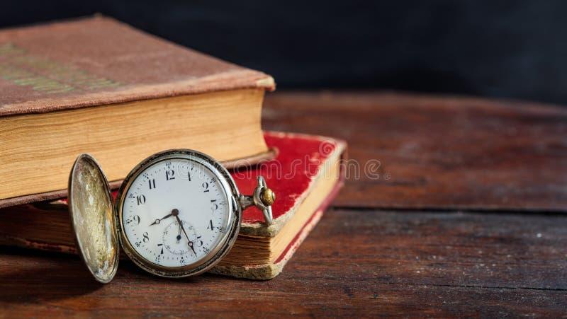 Rocznik książki i kieszeniowy zegarek na ciemnym tle fotografia royalty free