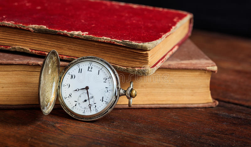 Rocznik książki i kieszeniowy zegarek na ciemnym tle zdjęcie royalty free