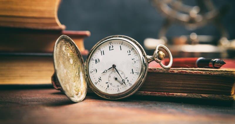 Rocznik książki i kieszeniowy zegarek na ciemnym tle obraz stock