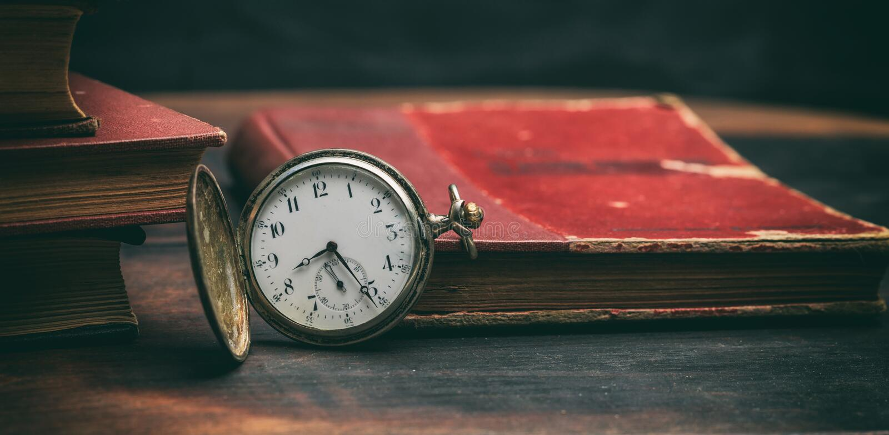 Rocznik książki i kieszeniowy zegarek na ciemnym tle obrazy royalty free