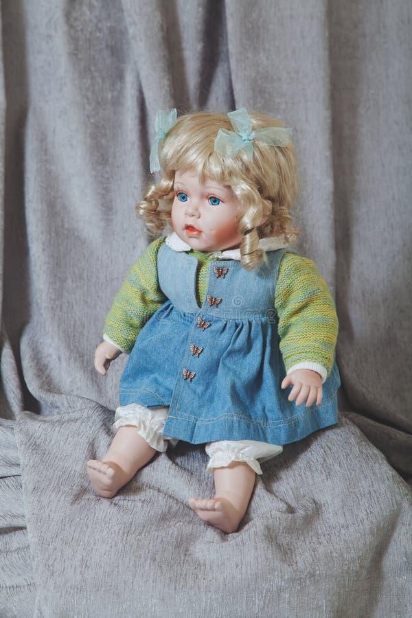 Rocznik porcelany lali blondynka na szarym tkaniny tle fotografia royalty free