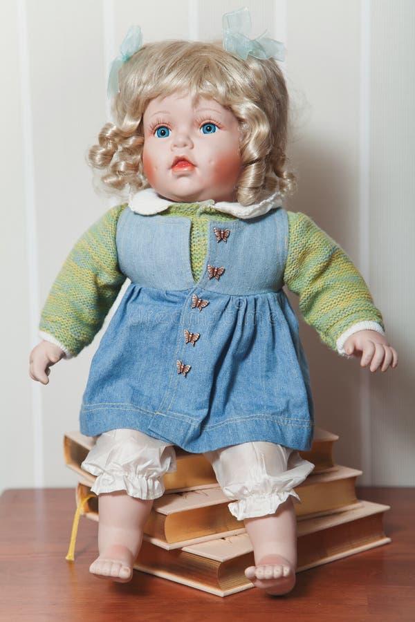 Rocznik porcelany lali blondynki obsiadanie na stercie książki zdjęcie stock