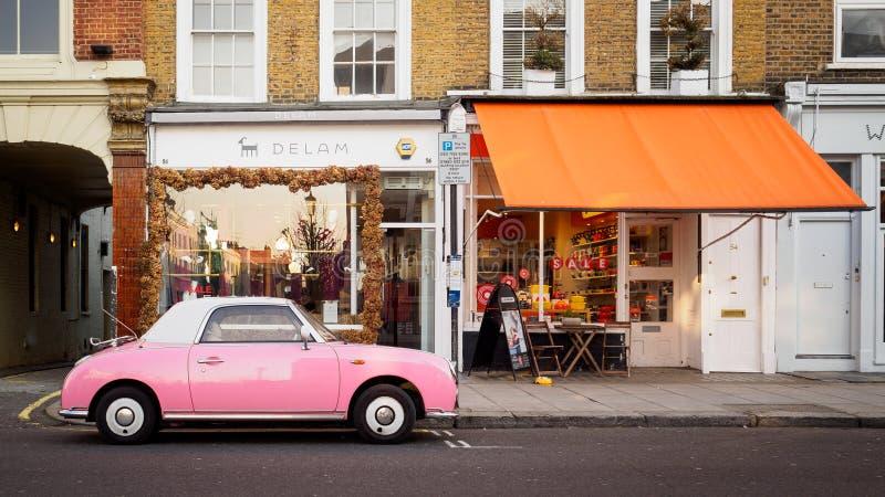 Rocznik różowy Nissan Figaro parkujący w drodze w Notting wzgórzu, Londyn UK Czerwiec 2017 zdjęcie royalty free