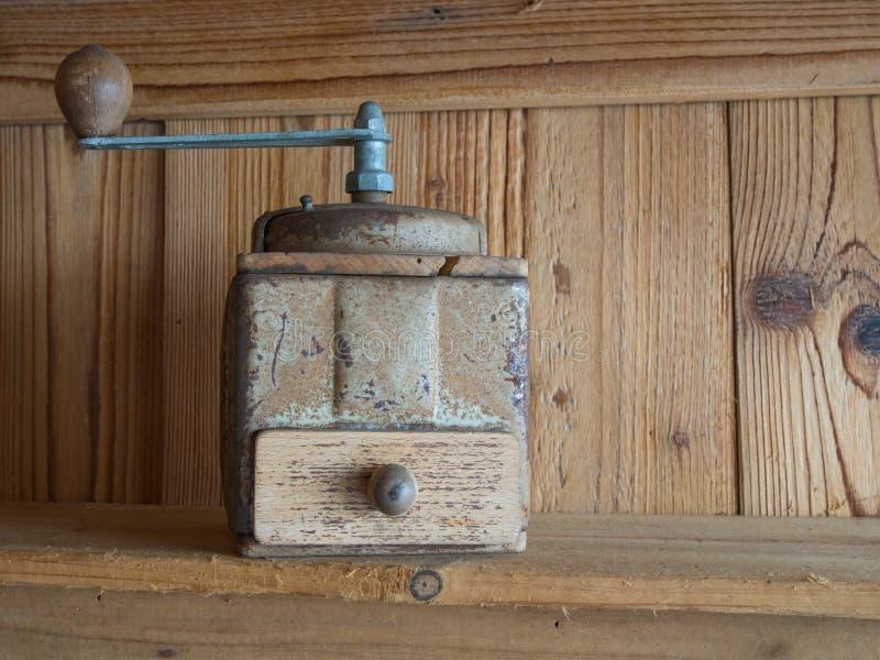Rocznik ręki cranck kawowy ostrzarz, drewnianych desek tło obraz stock