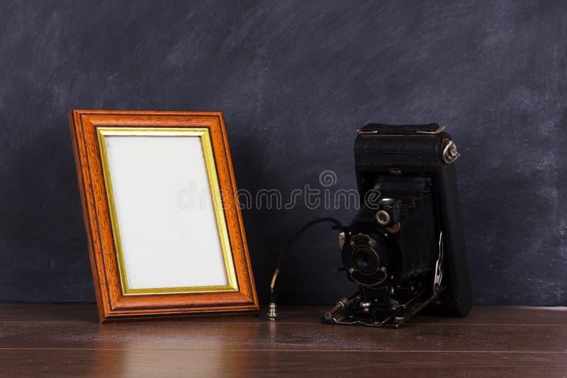Rocznik rama przeciw blackboard tłu i kamera obrazy stock