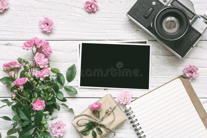 Rocznik retro kamera i menchii róża kwitniemy bukiet z pustą fotografii ramą, prążkowanym notatnikiem i prezenta pudełkiem, zdjęcie royalty free