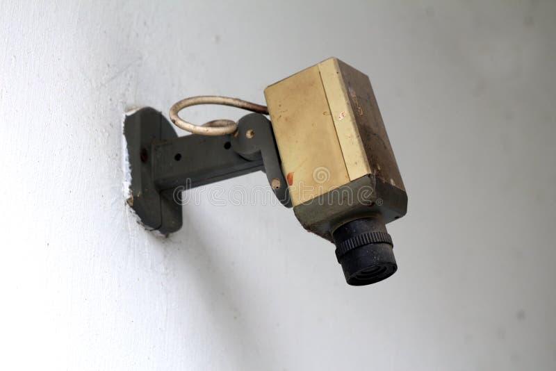 Rocznik retro mała czarny i biały kamera bezpieczeństwa wspinająca się na budynek ścianie i zakrywająca z gęstą warstwą pył obrazy royalty free