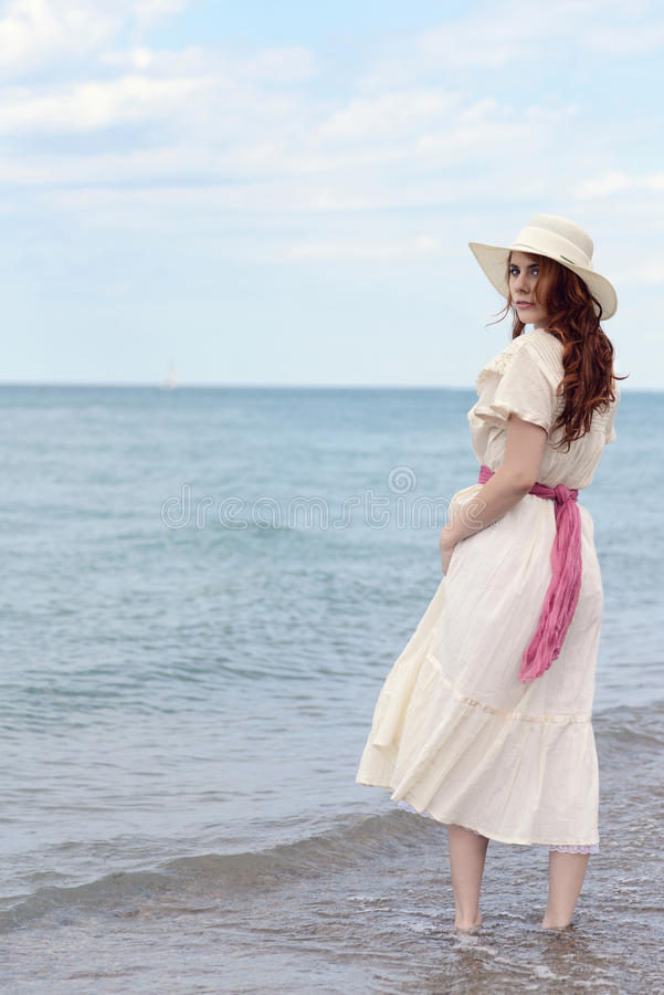 Rocznik rudzielec kobieta jest ubranym kapelusz przy oceanem zdjęcia royalty free