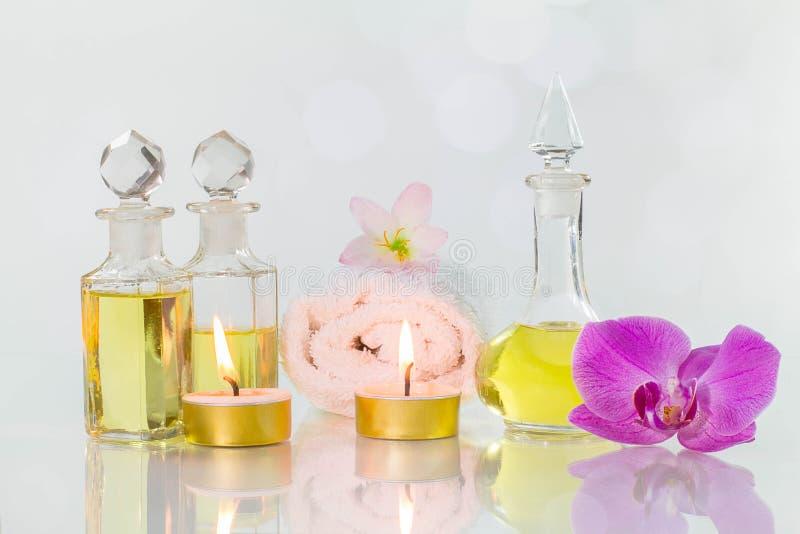 Rocznik stare butelki aromatyczni oleje z palić świeczkami, kwiatami i białym ręcznikiem na glansowanym bielu stole na białym tle zdjęcie stock