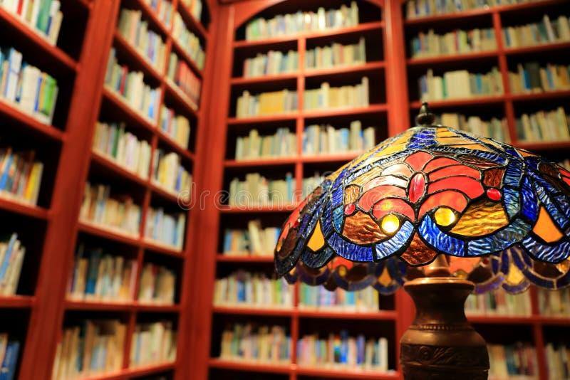 Rocznik stołowa lampa, książki i półka na książki w bibliotece, pojęcie stary biblioteczny czytelniczy pokój obraz royalty free