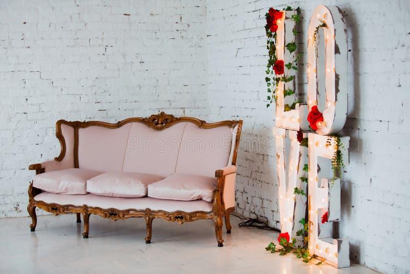 Rocznik stylowa kanapa dekorował z kwiatami w loft wewnętrznym pokoju z dużym okno obrazy royalty free