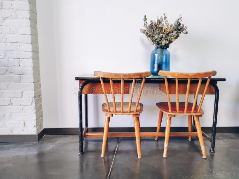 Rocznik szko?y podstawowej drewniany biurko i dwa drewnianego krzes?a z wysuszonym kwiatu przygotowania w b??kitnej wazie przeciw obraz royalty free