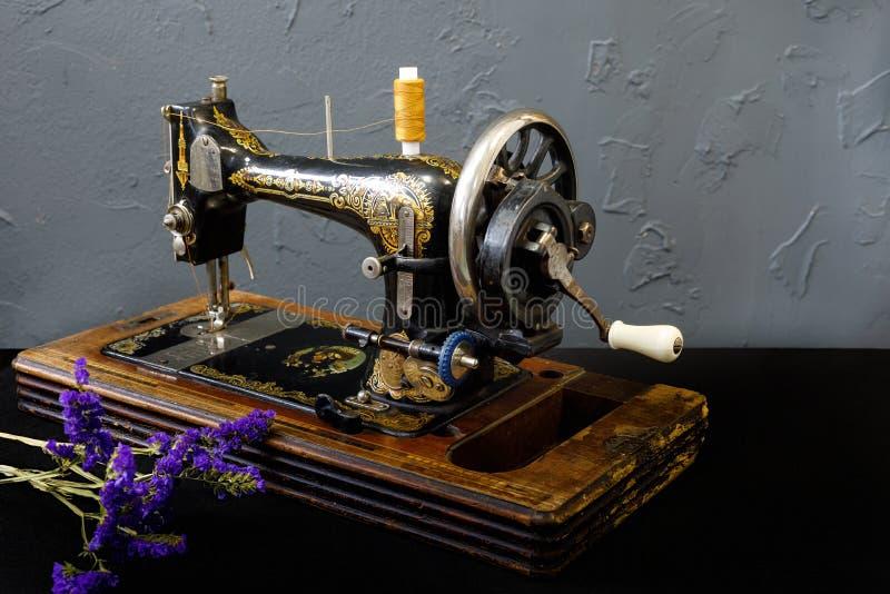 Rocznik szwalna maszyna stoi na białym stole fotografia royalty free