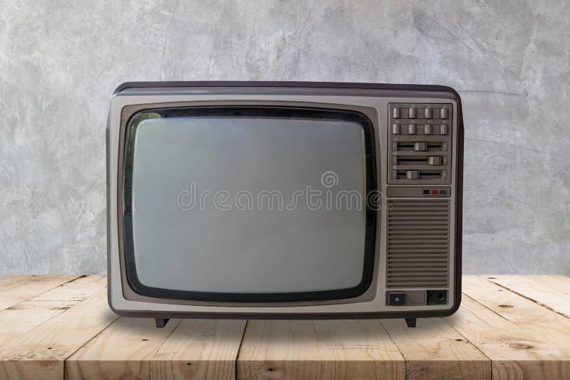 Rocznik telewizja na drewnianym stole i cement ściennej teksturze tle i zdjęcie stock
