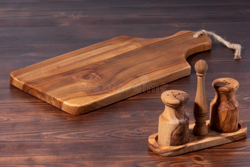 rocznik tnąca deska z sól pieprzu potrząsaczem na starym drewnianym tle, w górę zdjęcia royalty free