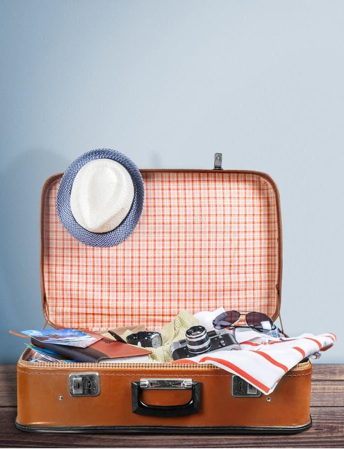 Rocznik walizka z podróżnym materiałem na świetle fotografia stock
