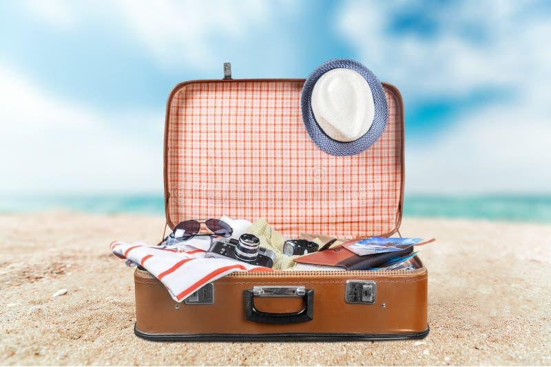 Rocznik walizka z podróżnym materiałem na plaży zdjęcia royalty free