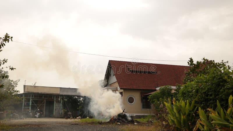 Rocznik wsi dom z palenie stosem słoma w ogródzie obraz stock