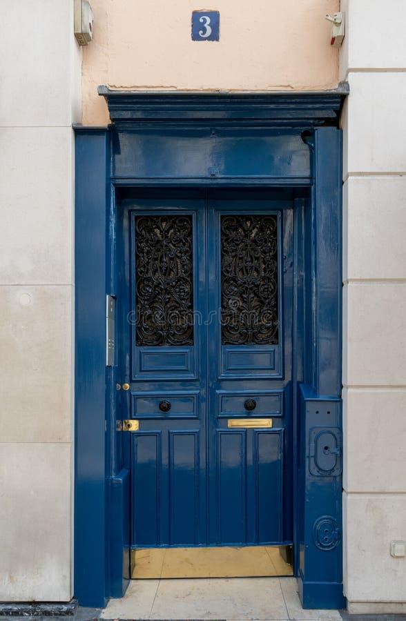 Rocznika błękit malował drzwi stary budynek pod liczby trzy nameplate w Paryskim Francja Antykwarski drzwi z ozdobnymi metal siat zdjęcie stock