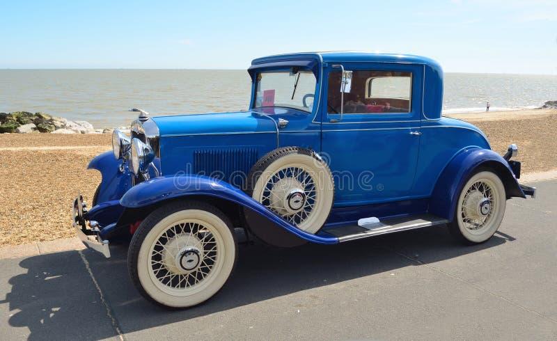 Rocznika Błękitny Motorcar z biel ściany oponami obraz stock
