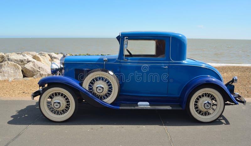 Rocznika Błękitny Motorcar z biel ściany oponami parkować na nadbrzeże deptaku obraz stock