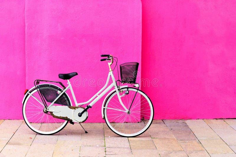 Rocznika biały bicykl przeciw wibrującej menchii ścianie zdjęcia stock