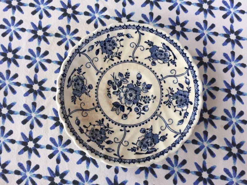 Rocznika biały i błękitny talerz na błękitnym tablecloth tle obraz royalty free