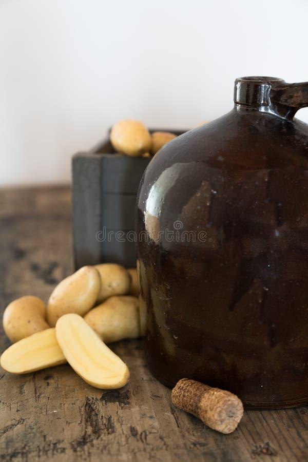 Rocznika bimberu dzbanek na nieociosanym drewnianym stole z grulami i kukurydzanego cob korkiem zdjęcie royalty free