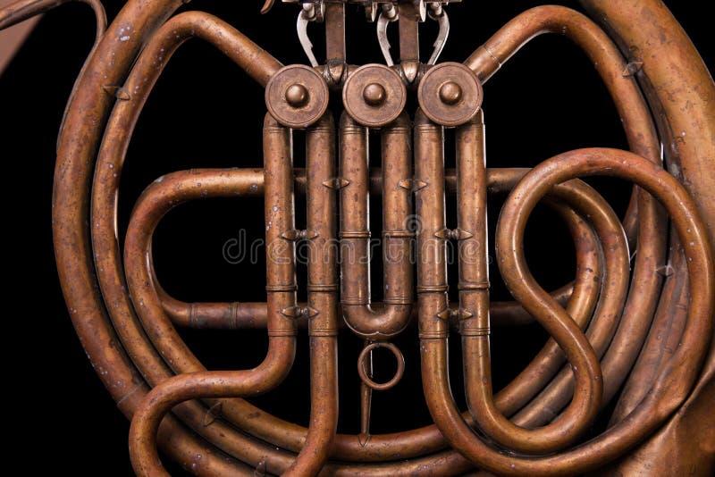 Rocznika brązu drymby, klapa, kluczowych machinalnych elementów francuski róg, czarny tło Dobry wzór, szybki muzyczny instrument zdjęcie royalty free