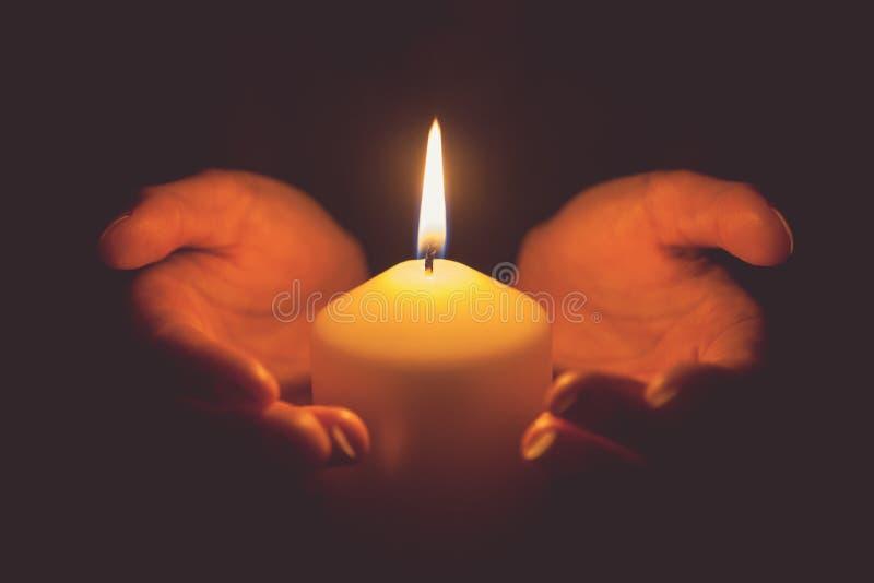 Rocznika brzmienie ręki trzyma płonącą świeczkę w zmroku zdjęcia royalty free