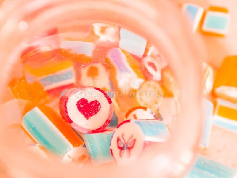 Rocznika brzmienie Zbliżenie przy czerwonym sercem i kolorowe cukierek trzciny w trawie zgrzytamy obraz royalty free