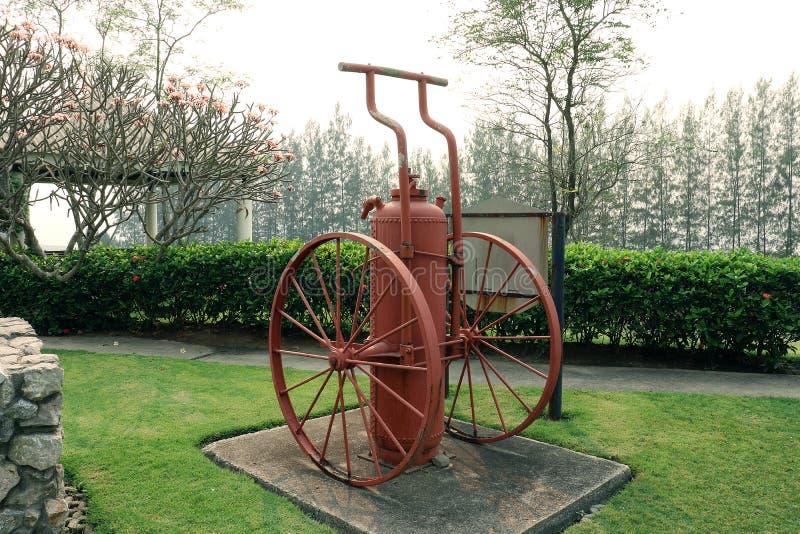 Rocznika czerwony pożarniczy gasidło, ntique czerwonego ogienia extinguishe na zieleń ogródzie fotografia stock