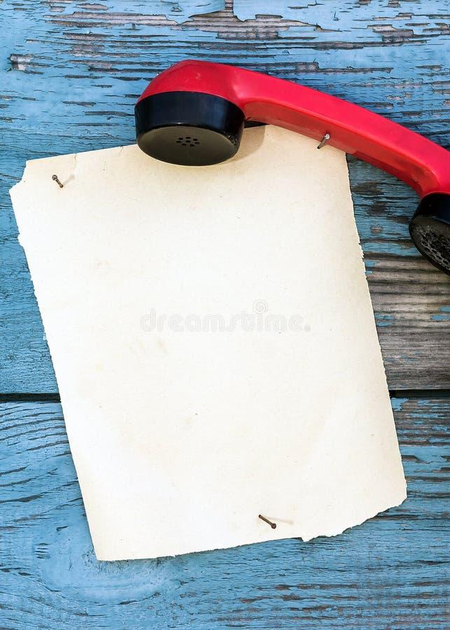 Rocznika czerwony telefon i kawałek papieru pisać zdjęcia royalty free