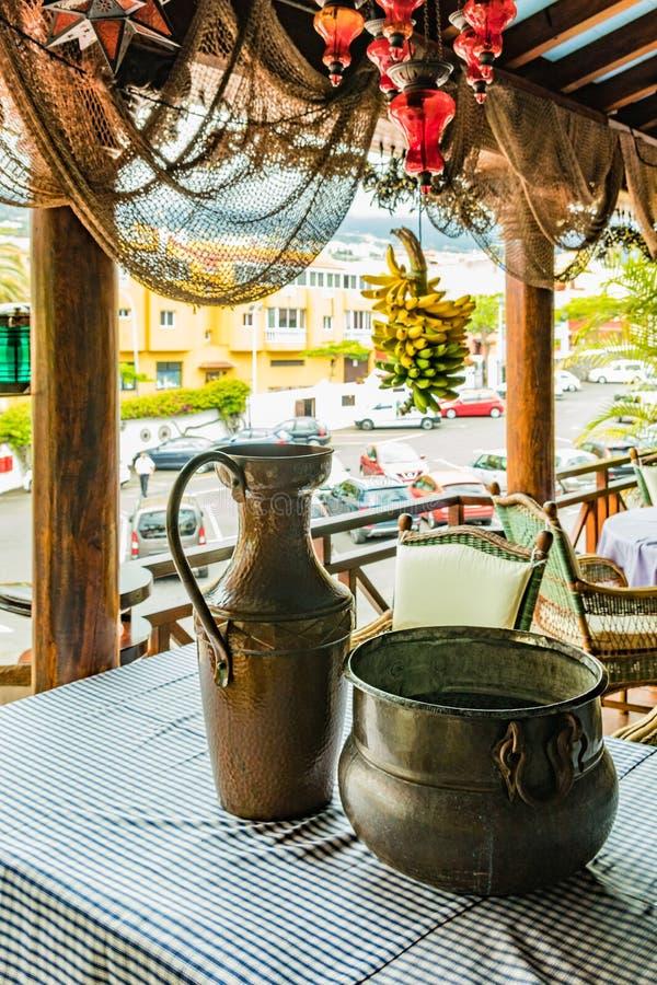 Rocznika dęciak i puszkujemy na stole z barwionym tablecloth Wisząca wiązka dojrzali banany i lokalna wioska w fotografia stock