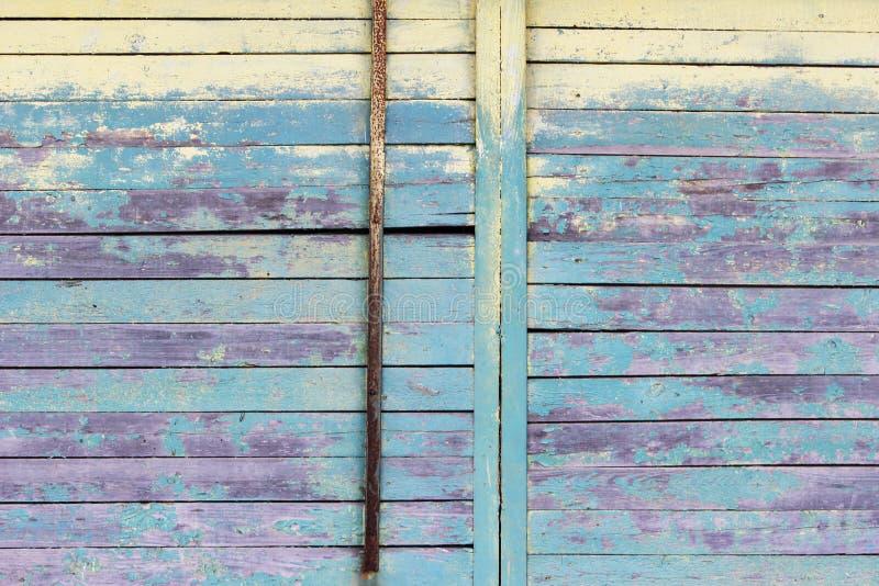 Rocznika drewniany tło z obieranie turkusem, żółtą starą płatkowatą farba i stara ośniedziała drymba domowa stara ściana fotografia stock