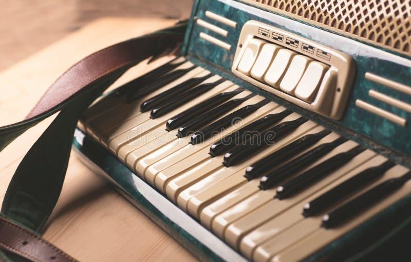 Rocznika instrumentu muzycznego akordeon na drewnianym stole fotografia royalty free