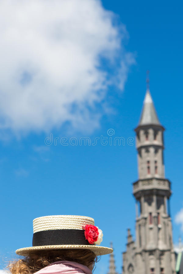 Rocznika kapelusz i czerwony kwiat z urzędem miasta w Brugge obraz stock