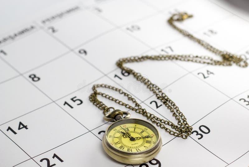 Rocznika kieszeniowy zegarek kłaść na kalendarzowej stronie z datami obrazy royalty free